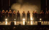 A dozen or so members of the all-female Vocal Point a cappella group lit up on a dark stage.