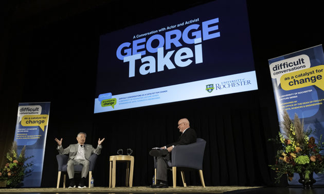 George Takei and Dean Donald Hall seated on stage under a screen that reads George Takei