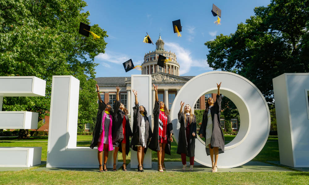 Six graduates in bright outfits and regalia toss their caps into the air.