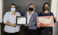 three women, wearing face coverings, stand together holding signs