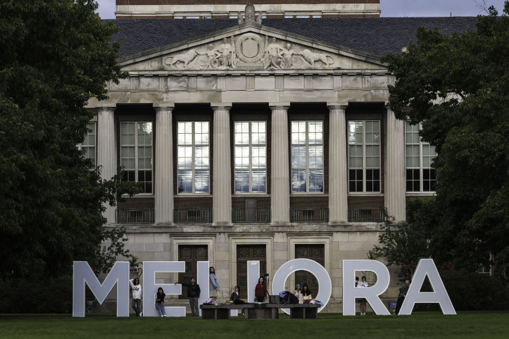 Large letters spell out MELIORA with people posing near them during Meliora 2021.