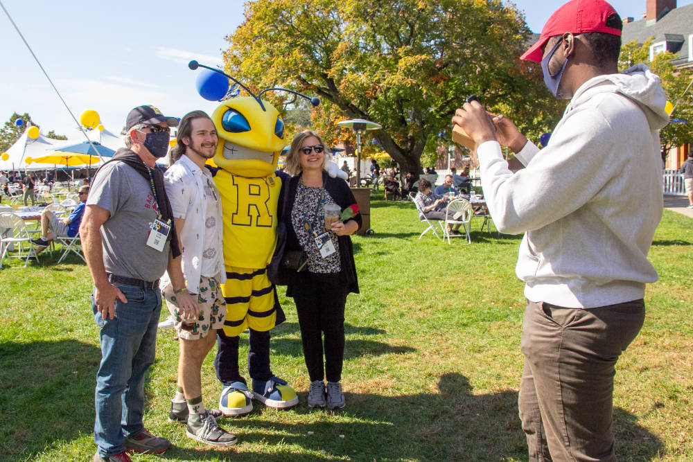 Three people with Yellowjacket mascot Rocky pose while someone takes a photo of them during Meliora 2021.