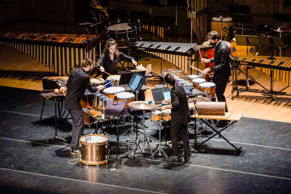 Four members of the Eastman Percussion Ensemble play instruments together on stage.