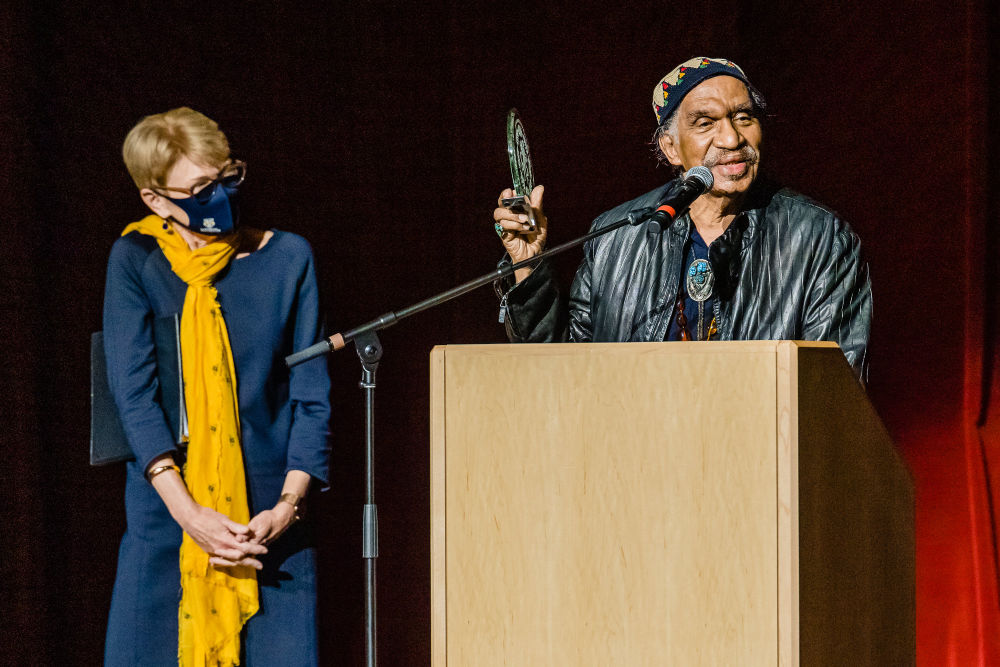 Sarah Mangelsdorf in a blue dress, yellow scarf, and mask looks at Garth Fagan, who is standing next to her at a podium holding an award.