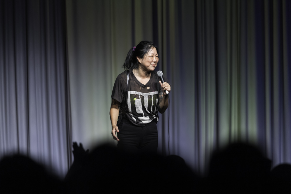 Margaret Cho smiles and holds a microphone on stage.