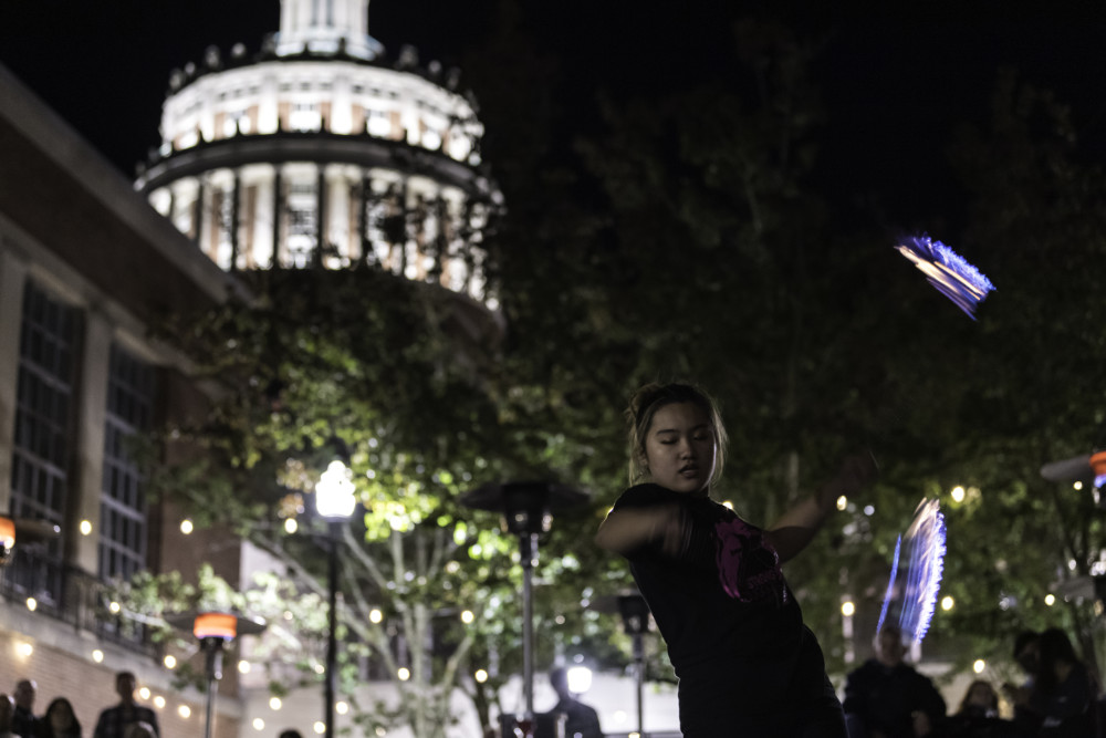 Student juggles fire props at night with onlookers to the side and Rush Rhees Tower lit up in the background.