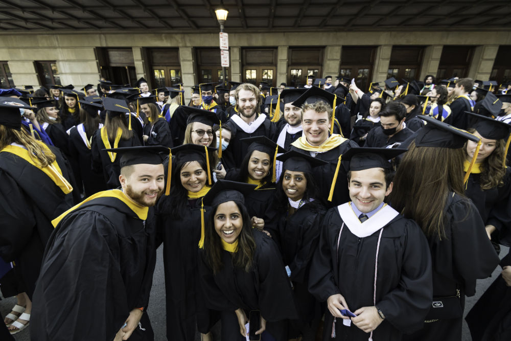 Several students garbed in regalia huddle together to smile for a group photo during Meliora 2021's commencement ceremony.