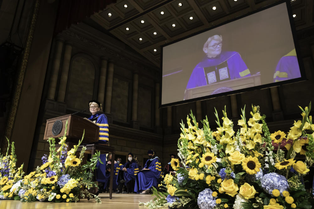Regalia-clad Sarah Mangelsdorf stands at a podium on a flower-covered stage while her image projects on a big screen behind her for Meliora 2021 commencement.
