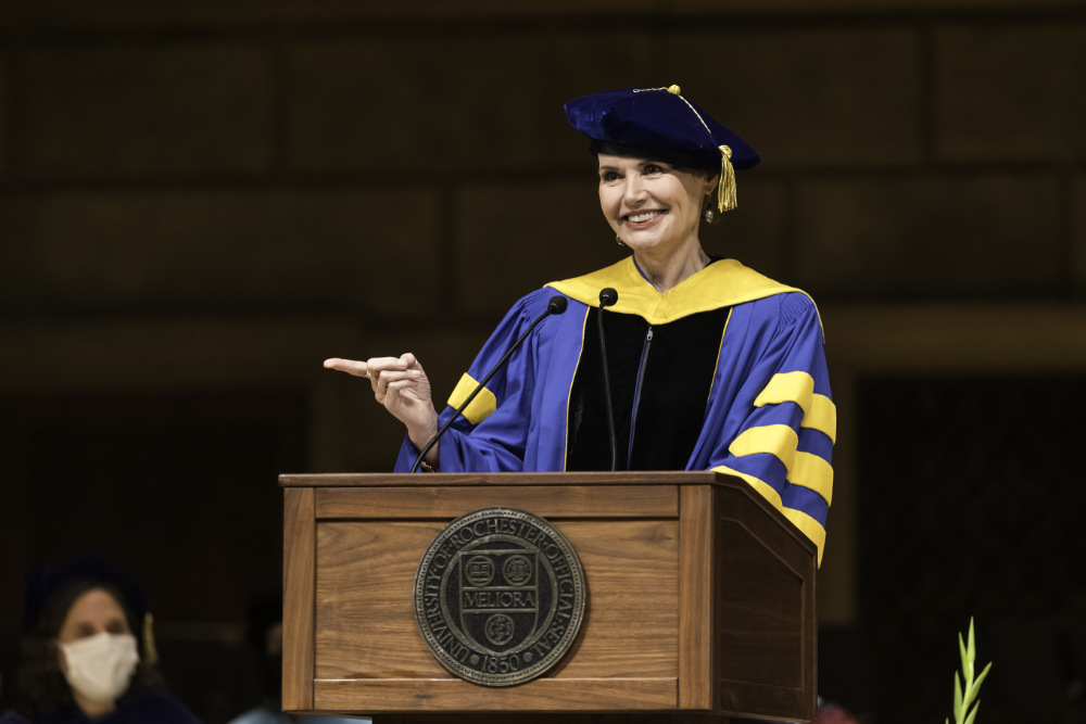 Geena Davis wears University of Rochester regalia while standing at a podium, smiling, and pointing at the audience.