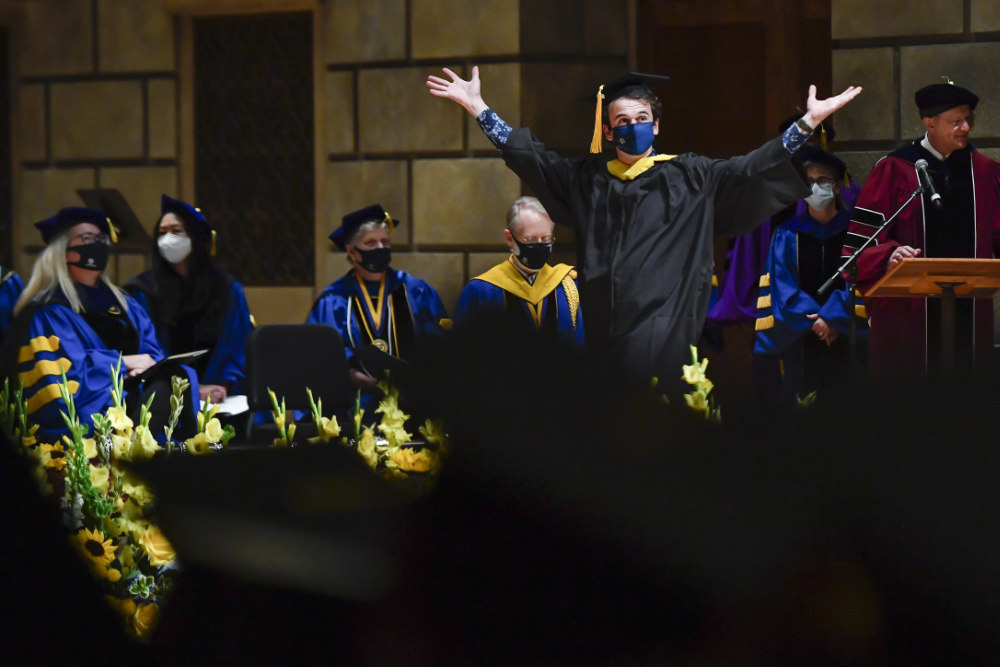 Class of 2020 graduate walks across the stage with arms raised as part of commencement.