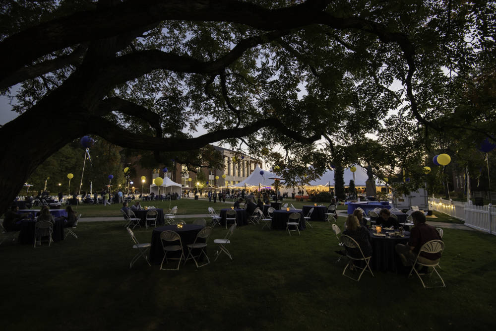 Meliora Village tables, tents, decorations, and guests at dusk with tree branches in the foreground.
