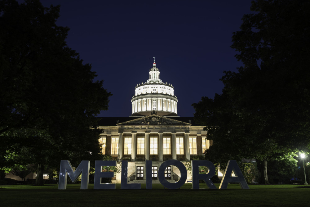 Meliora letters lit up from behind by Rush Rhees Library at twilight.