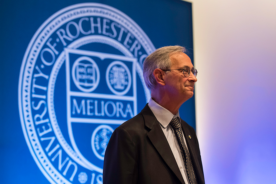 Joel Seligman stands on stage in front of MELIORA shield