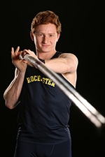 Jarod Forer holding a pole vault in a Rochester track and field uniform