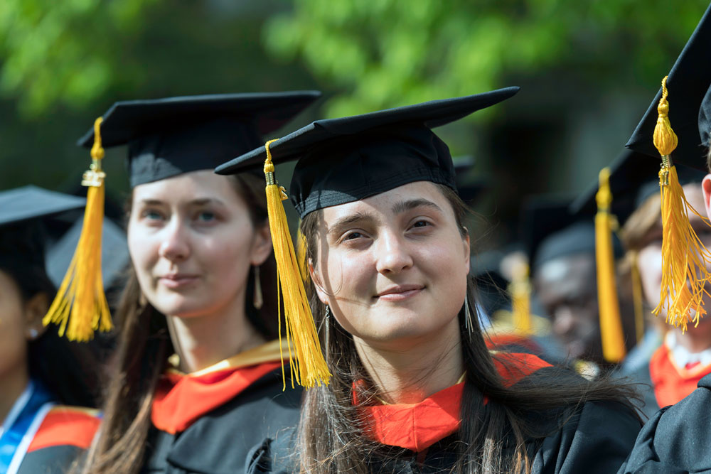 two female graduates at commencement ceremony