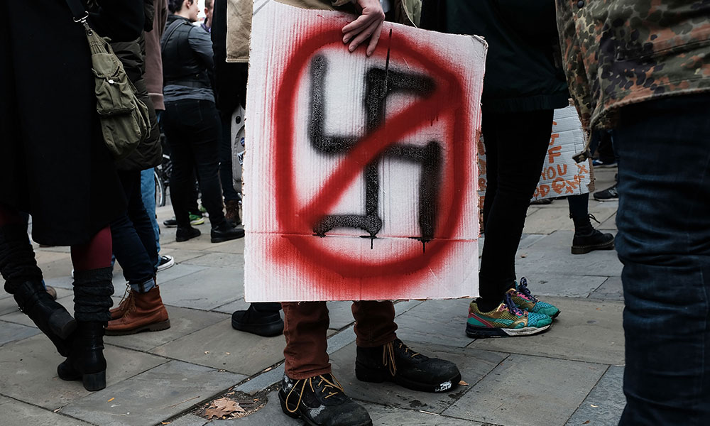 protester at an march against anti-antisemitism holds a sign with a swastika crossed out in red
