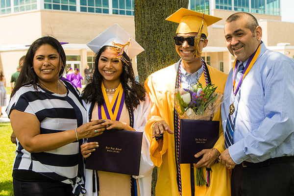 Two graduates in cap and gown with parents