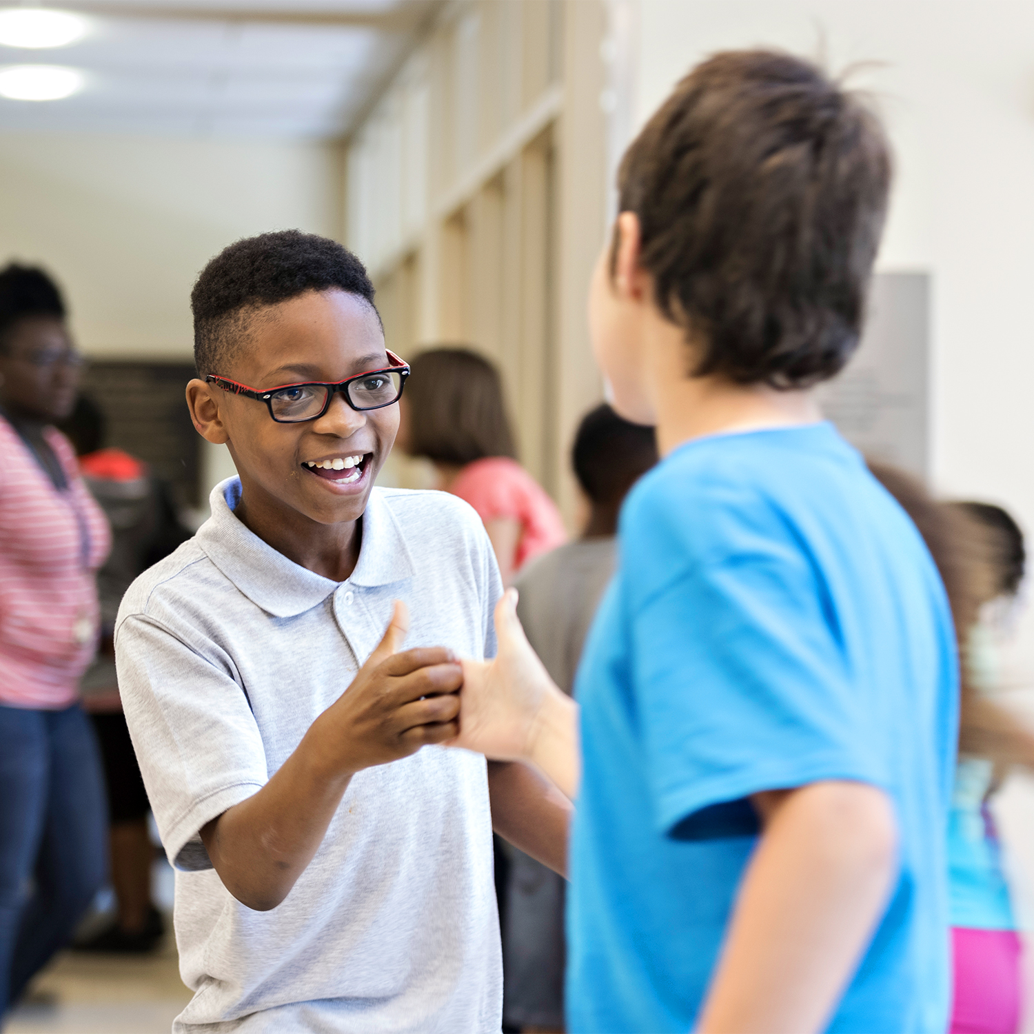 Two young boys shaking hands and smiling in the hallway.