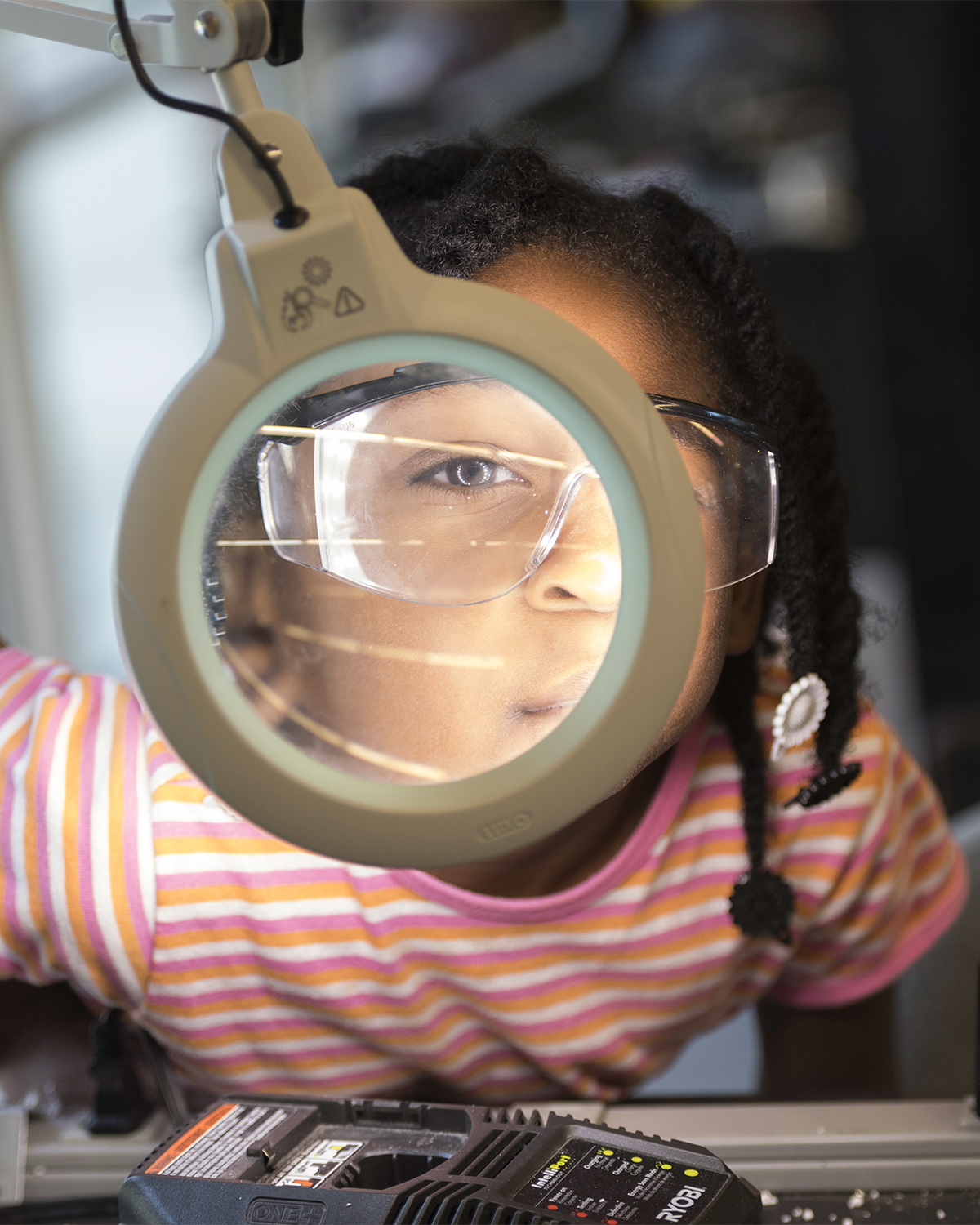 Young girl in safety glasses looking through an illuminated magnifying glass in the workshop in Rettner Hall.