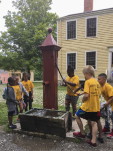 Students playing with an old well at Genesee Country Village and Museum.