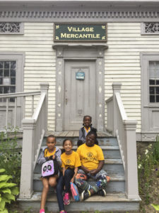 """Students smiling on the steps of an old building with a sign on the building that reads """"Village Mercantile"""" at Genesee Country Village and Museum."""