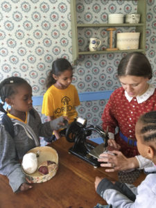 A woman in turn of the century clothing demonstrated an old fashioned sewing machine to children.