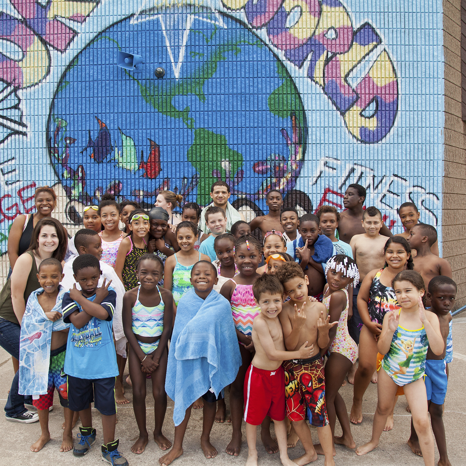 A group of young students in swimsuits posing in front of a mural at the swimming pool.