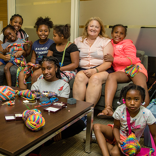 Children gathered around volunteer on a couch who taught them how to crochet