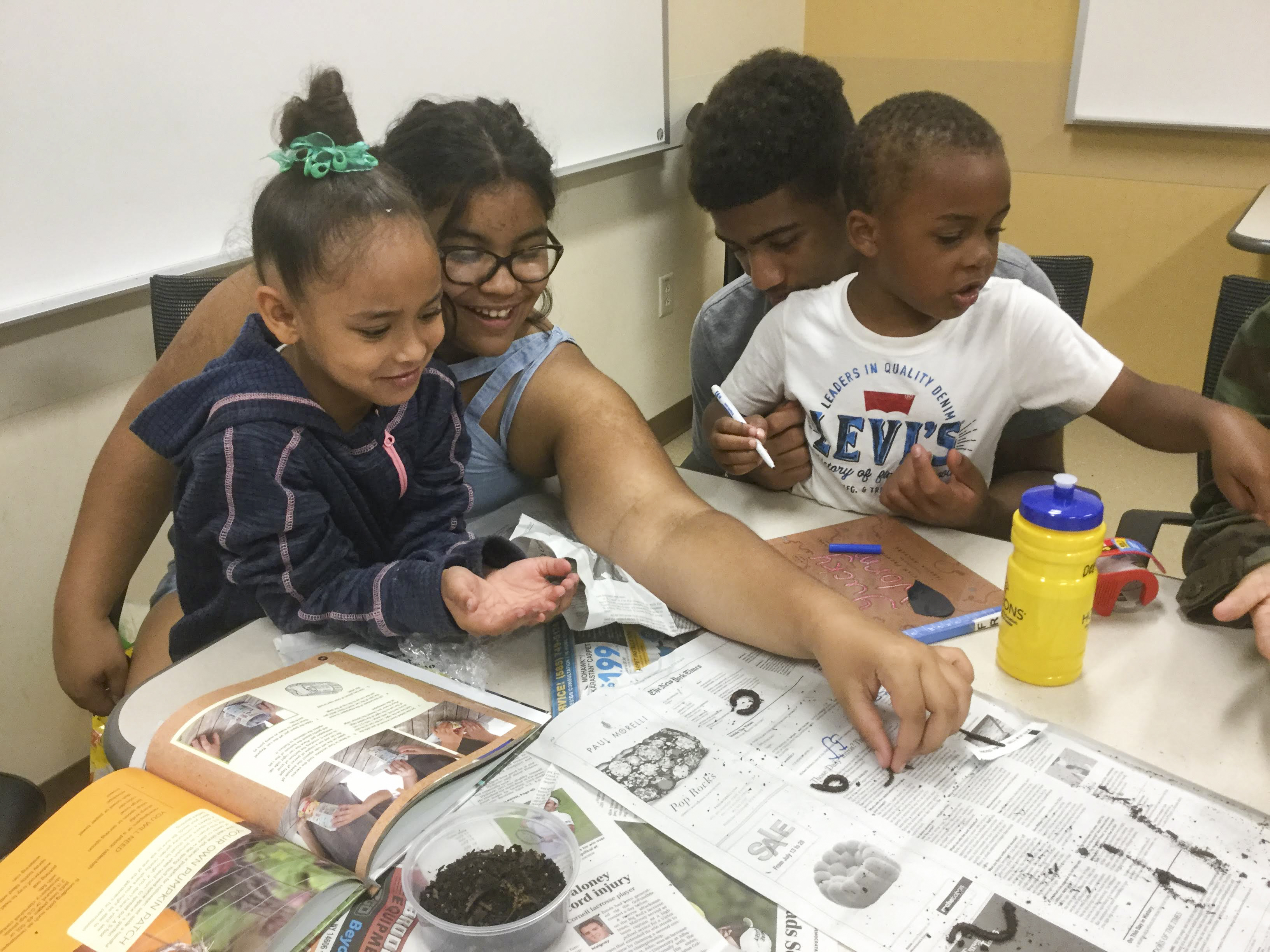 Older students helping younger students learn about worms and soil.