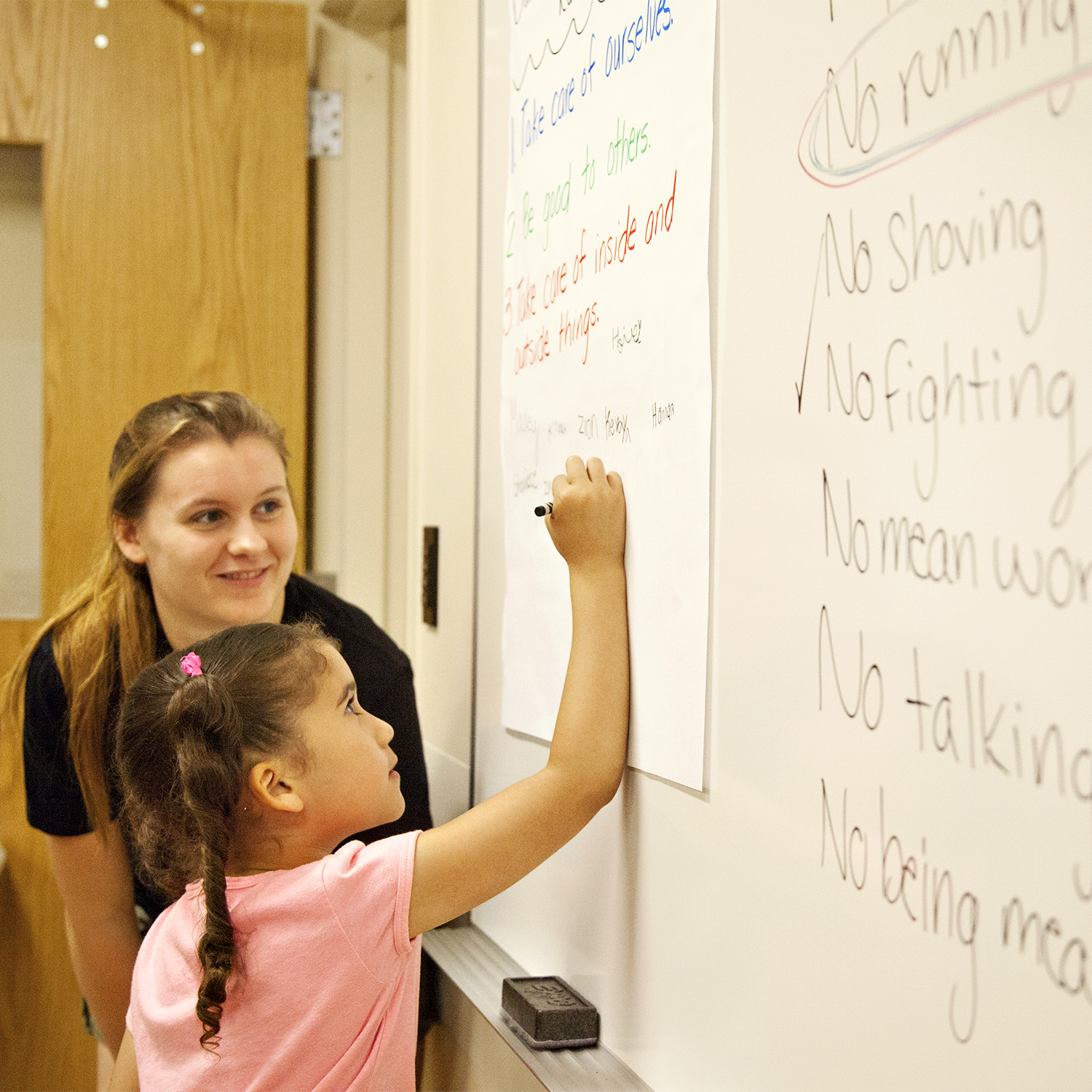 A teacher with a young student writing on the white board.