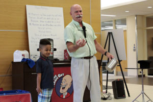 Little boy standing next to Magician while he performs