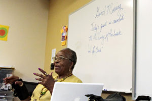 Older woman author speaking in front of a classroom.