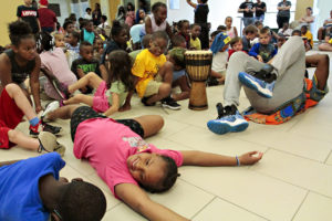 Children laughing and laying on the floor during an activity