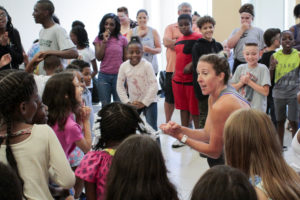 Woman leading a circle of kids in dancing.