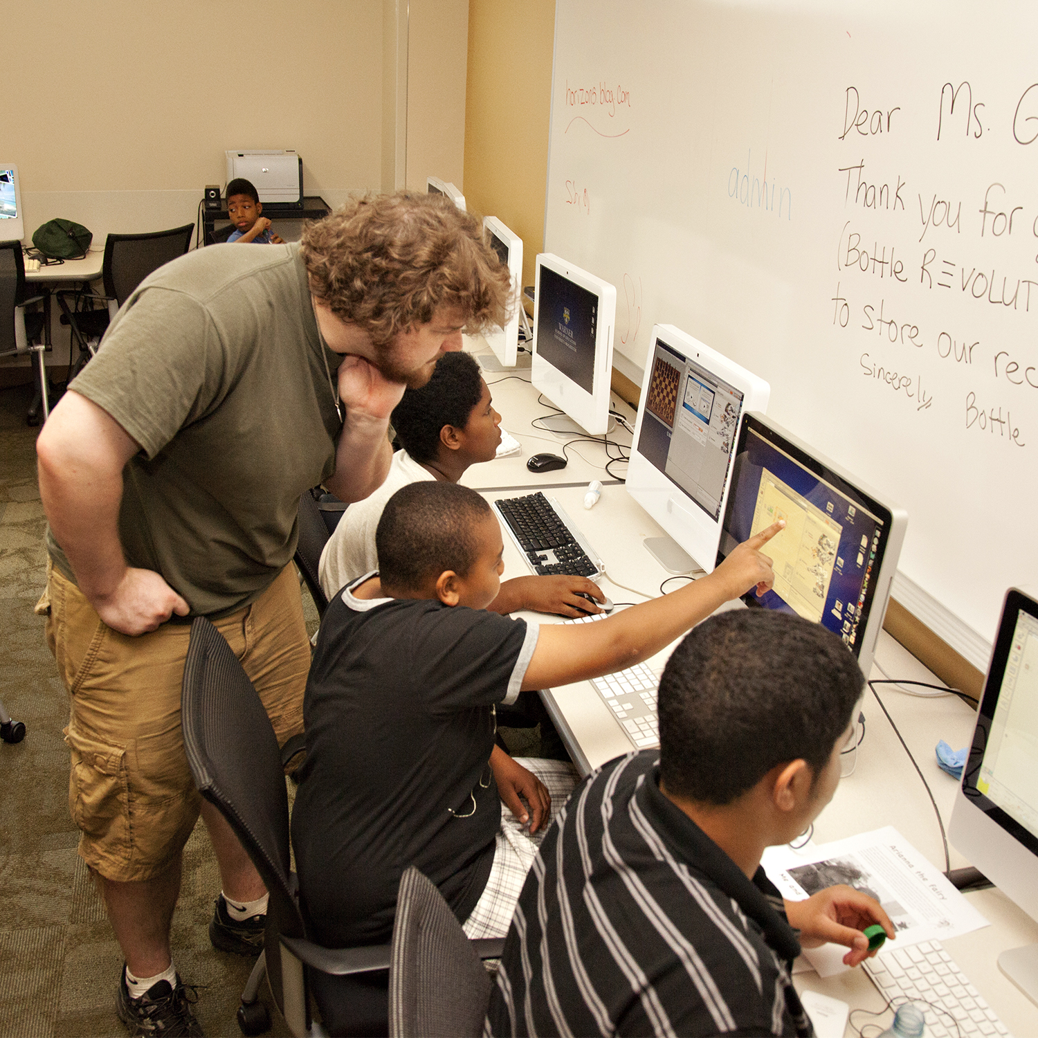 A teacher leans over to help a student working with others in the computer lab.