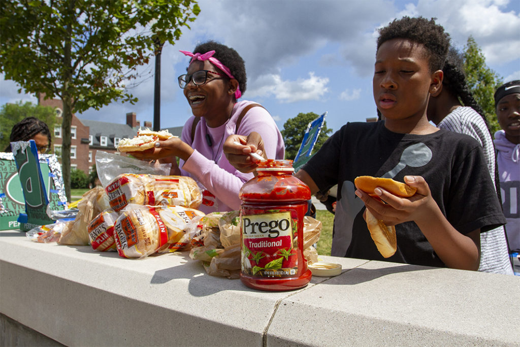 Students laughing while preparing their pizzas outside.