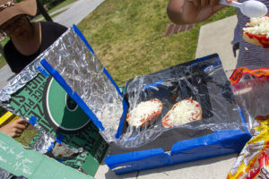Two bagel pizzas cooking in their solar pizza box ovens.