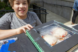Young student smiling with his pizza box oven, steam can be seen through the plastic wrap.