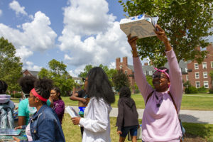Students outside LeChase hall holding up their pizza box ovens up to the sun.