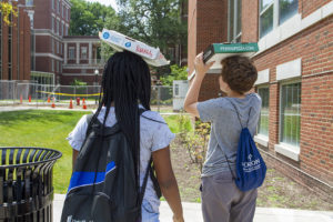 Two students with their solar-pizza box ovens on their heads facing the sun.