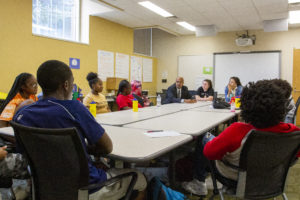 The Dean of the Warner school speaking with a table of young students