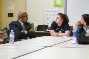 The Dean of the Warner School speaking with a young student at a table in the classroom