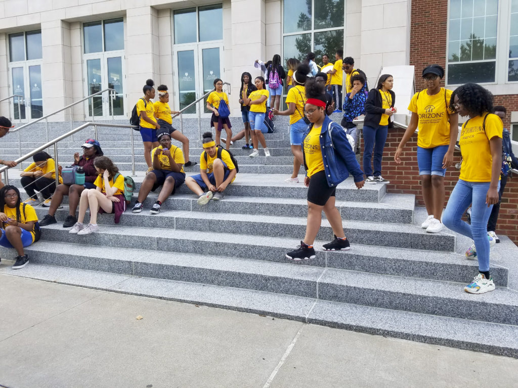 Horizons students in yellow tshirts mingling on the stairs in front og LeChase Hall before their field trip.