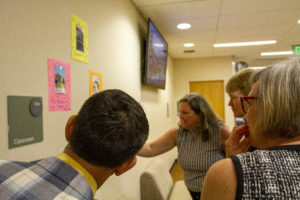 Adults looking at student work on a wall