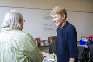 president of the university laughing with another teacher in the classroom.