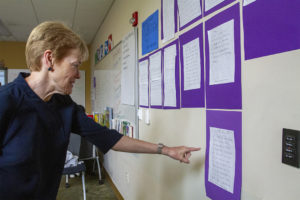 President of the university reading student writing on posted on the classroom wall.