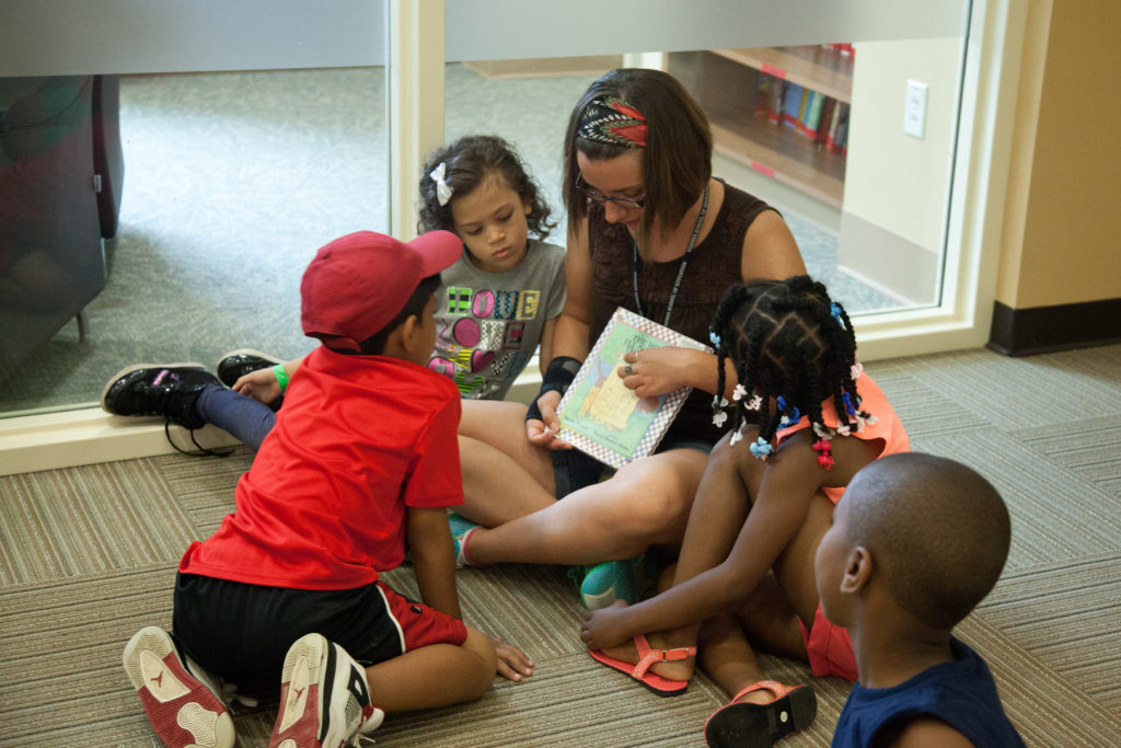 Woman sitting on the floor reading to a group of small children gathered closely around. her