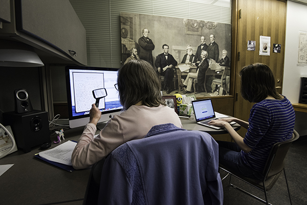 two people working to transcribe scans of historical documents