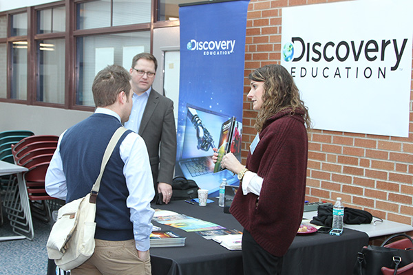 people talking at a conference at a Discovery Education table