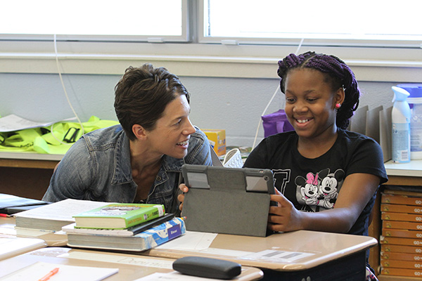 a teacher and student smile while working at an ipad